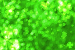Bokeh effect with blurred clovers. St. Patrick's Day background Stock Photos