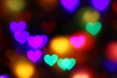 Bokeh en forma de corazón colorido de las tarjetas del día de San Valentín en el bokeh negro de la iluminación del fondo para la  Imagenes de archivo