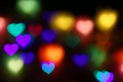 Bokeh en forma de corazón colorido de las tarjetas del día de San Valentín en el bokeh negro de la iluminación del fondo para la  Foto de archivo