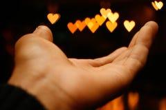 Bokeh för vänstersidahandman hjärta överst Royaltyfria Bilder