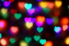 Bokeh in forma di cuore variopinto dei biglietti di S. Valentino sul bokeh nero di illuminazione del fondo per la decorazione al  Fotografia Stock