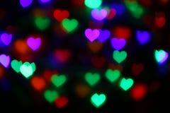 Bokeh in forma di cuore variopinto dei biglietti di S. Valentino sul bokeh nero di illuminazione del fondo per la decorazione al  Immagini Stock