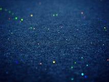 Bokeh-Funkeln auf dunkelblauer Baumwollgewebebeschaffenheit stockfoto