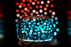 Bokeh and glass vase with drops on black background. Magic picture, fabulous color effects.. Magical holiday atmosphere in the simple things Stock Photos
