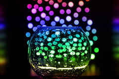 Bokeh and glass vase with drops on black background. Magical holiday atmosphere in the simple things Stock Photography