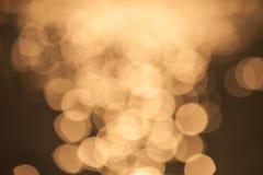 Bokeh-Goldfarbzusammenfassungshintergrund stockfotografie