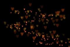 Bokeh hearts. Bokeh heart shaped lights on black background stock image