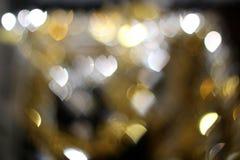 Bokeh hearts sparkling in the background. Bokeh hearts sparkling in the dark background Royalty Free Stock Photos