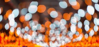 Bokeh ilumina-se, luzes cintilantes do ponto do borrão no fundo abstrato alaranjado Foto de Stock Royalty Free