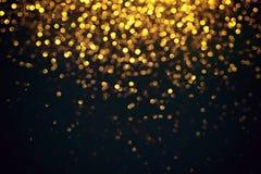 Bokeh léger d'or abstrait sur le fond noir Photos libres de droits