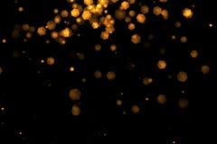 Bokeh léger d'or de particules d'éclat de Noël loopable à partir du dessus sur le fond noir, Ne heureux de partie de salutation d illustration stock