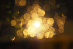 抽象圆黄色bokeh在黑暗的背景,金泡影l中 免版税库存照片