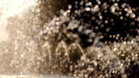 Bokeh laisse tomber le fond de mouvement de la fontaine éclairé à contre-jour banque de vidéos