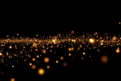 Bokeh leggero dorato delle particelle di lustro di Natale su fondo nero, festa fotografie stock
