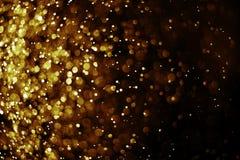 Bokeh-Lichtgoldfarbschwarzhintergrund stockbilder