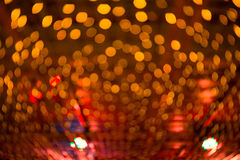 Bokeh light, shimmering blur spot lights on orange abstract background. Stock Image