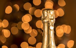 Sealed top and cork of champagne bottle against christmas tree. Bokeh lights from Christmas tree behind the gold foil covered neck of champagne bottle Royalty Free Stock Photography