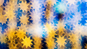 Bokeh of lights on defocused background in a form of suns. Beautiful bokeh made of warm orange blurred lights in the form of suns on blue background, special Stock Images