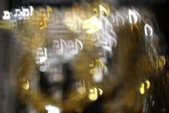 Bokeh notes on a glittering background. Bokeh notes on a glittering dark background Royalty Free Stock Photo