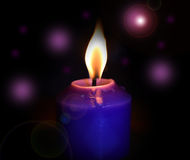 Bokeh purple candles over black background. Bokeh purple candles over a black background Royalty Free Stock Photo
