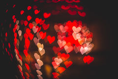 Bokeh rojo y blanco de los corazones en la textura oscura para el uso en diseño gráfico Foto de archivo libre de regalías