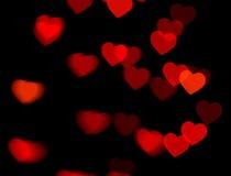 Bokeh rouge de coeur sur l'obscurité photographie stock