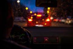 Bokeh se enciende del atasco a través de un parabrisas del coche en noche lluviosa en la ciudad grande Imagen de archivo