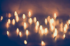 Bokeh shaped pines, golden lamp. During Christmas Stock Photo