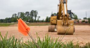 Bokeh shot of a warning flag in front of an excavator. stock images