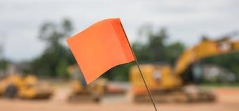 Bokeh sköt av en varnande flagga framme av en rad av tung konstruktionsutrustning royaltyfri foto