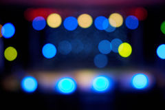 Bokeh of spaced blurred stage lights. Spaced colorful defocused lights on dark background stock photography