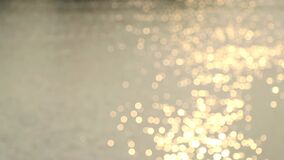 Bokeh of sunlight reflected on the water surface.