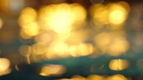 Bokeh of sunset light reflect in waving swimming pool. Blurred to focus background. slow motion. 3840x2160 stock footage