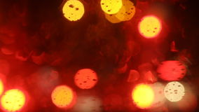Bokeh from traffic and street lights and car at night. Automotive wiper cleans the car windscreen from rain drops stock video footage