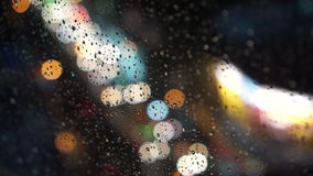 Bokeh Through Wet Window. Subject: Rain drop on the window with the bokeh of traffic in the background. Shot: Bokeh, Blurred Background