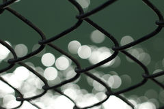 Bokehlicious. Sparkling water behind a fence royalty free stock photo