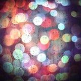 在玻璃和五颜六色的bokeh光的Waterdrops 库存照片