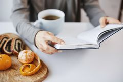 Boken är som kammare av kunskap Smart modern kvinnlig läs- favorit- roman under frukosten som tycker om att dricka som är varmt royaltyfria bilder
