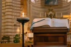 Boken av katolsk kyrkaliturgi nära den brinnande lampan i arkivfoto