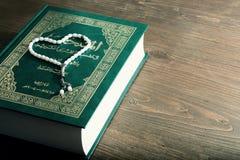 Boken av Koranen med vita pärlor på en trätabell Arkivbilder