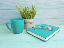 Bokexponeringsglas lägger in med gräskopp kaffetappning på tabellträbegrepp Arkivbilder