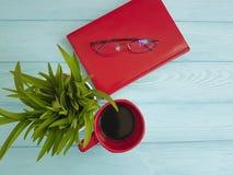 Bokexponeringsglas lägger in med gräskoppen kaffe på träbegrepp Royaltyfri Bild
