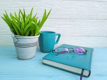 Bokexponeringsglas lägger in med växtkopp kaffetappning på tabellträbegrepp Arkivfoto