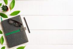 Bokexponeringsglas och penna för lägenhet lekmanna- på en vit wood bakgrund Arkivfoto