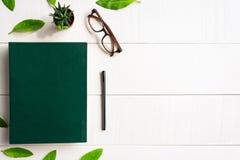 Bokexponeringsglas och penna för lägenhet lekmanna- på en vit wood bakgrund Royaltyfri Bild