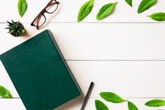 Bokexponeringsglas och penna för lägenhet lekmanna- på en vit wood bakgrund Royaltyfria Foton