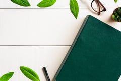 Bokexponeringsglas och penna för lägenhet lekmanna- på en vit wood bakgrund Royaltyfri Foto
