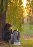 bokflickan läser den tonårs- treen under pilen Arkivfoto