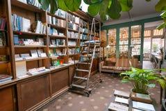 Bokhandel med antika bokhyllor, garnering, soffan och tabellen för kaffe och lunch av avläsare Arkivbilder