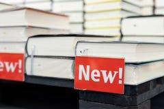 Bokhandelhylla med högen av nya böcker med den röda plattan Nya ankomster på bokhandeln Presentation av boken royaltyfria bilder
